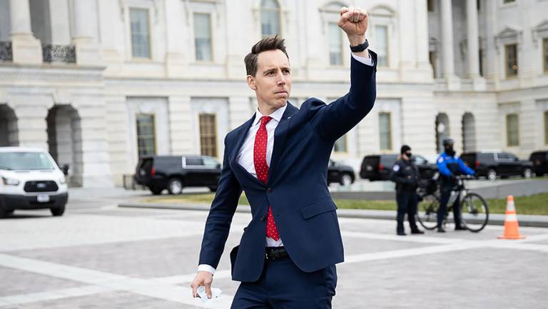 Senator Josh Hawley raising his fist in support of a crowd gathering at the US Capitol on Jan. 6, 2021. Image from https://www.kansascity.com/news/politics-government/article248354085.html